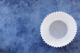 Empty White Cupcake Case over Blue Background