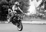 Fototapety Balancing gracefully. Young stuntman practicing tricks on the road monochrome soft smudged focus shot