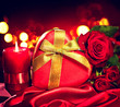 Valentine gift box and rose flower on red silk background