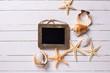 Empty blackboard and seashells on wooden background