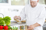 Professional chef preparing food in large kitchen