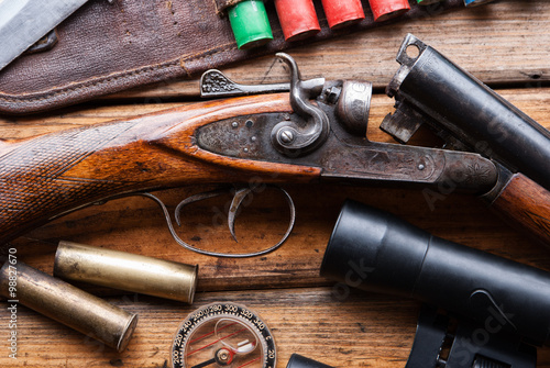 Poster The hunting rifle, cartridge belt,binoculars on a wooden table