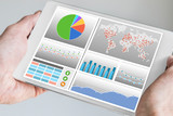 Fototapety Hand holding modern tablet or mobile device with analytics dashboard for sales, marketing, accounting, controlling department to check revenue, sales and business KPIs