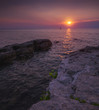 Beautiful Vibrant Sunset Over the Sea with Rocks in Foreground