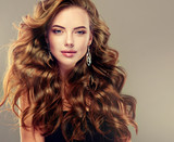 Fototapety Beautiful girl with long wavy hair .  Brunette with curly hairstyle . jewelry earrings