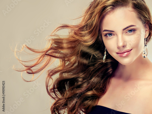 Beautiful girl with long wavy hair .  Brunette with curly hairstyle . jewelry earrings © Sofia Zhuravetc