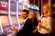 Постер, плакат: four young people playing slot machines in casino