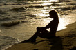 Beautiful, long haired slim young woman at the beach, sunset