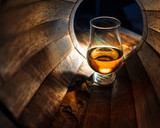 Fototapety A glass of whiskey in oak barrels