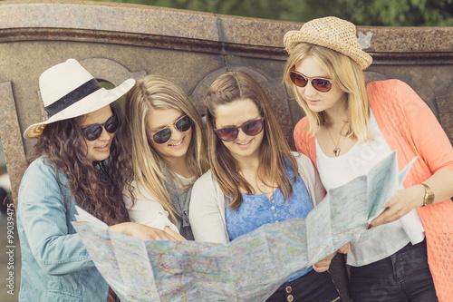 Poster Vier junge Touristinnen mit Stadtplan