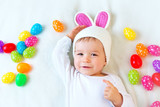Fototapety Baby boy in bunny hat lying on green blanket with easter eggs