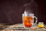 Steaming tea and honey on a wooden table - 99193669
