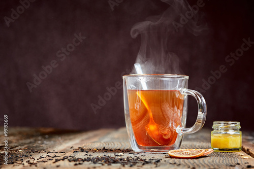 Steaming tea and honey on a wooden table Poster