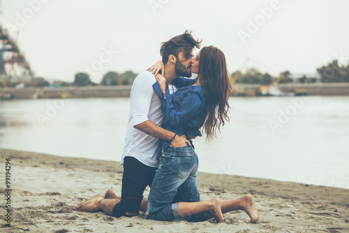 Plakat Young couple kissing on the sand by the river