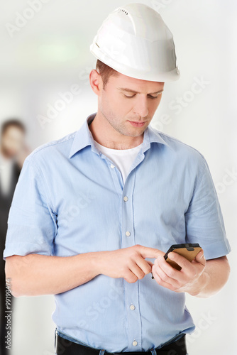 Poster Contractor in hardhat using his cell phone