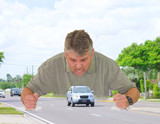 Road rage with angry man slamming his fists down on the road around a car as he screams at the car driver