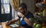 Chico moreno desayunando un café en la cocina, la luz entra por la ventana, hay un frutero