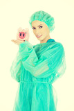 Female doctor with pink piggy bank.