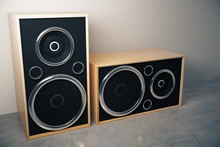 Old style stereo speakers on concrete floor