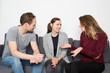 Leinwanddruck Bild - Drei Freunde sitzen auf Sofa und reden