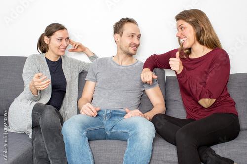 Leinwanddruck Bild Drei Freunde sitzen auf Sofa und reden