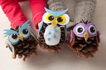 Children holding felt an pine cone owl craft © Saltodemata