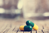 Pharmacy background. Pills on a wooden table. Medicine. Natural background. Capsule. Close up