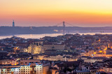 Fototapety Sunset with orange tones from the Monte Agudo viewpoint in Lisbon, capital of Portugal. In the background the 25th of April Bridge and The Christ the King statue, symbols of the city