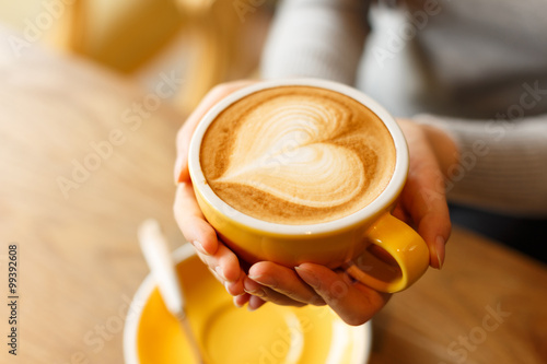 Sticker lady's hands holding cup with sth heart-shaped