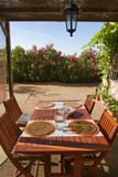 Mesa en Portico Exterior de una Casa con alguna Vajilla Puesta preparada para cuatro comensales, con sillas, en el jardin exterior de una casa.  Pan, jarra y copa con agua. Rodeada de azaleas