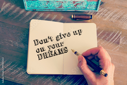 Motivational message DON'T GIVE UP ON YOUR DREAMS written on notebook Poster