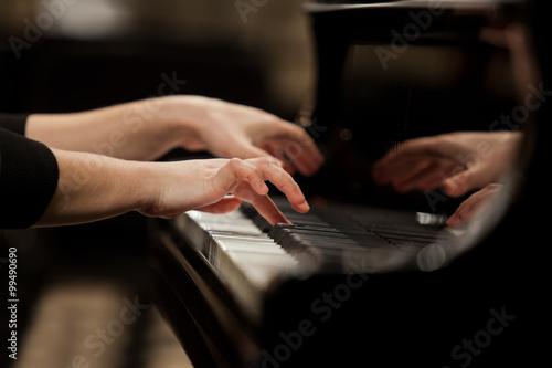 Hands girl playing piano closeup