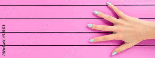 Staande foto Manicure Female hand with blue nails over pink background