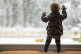 Toddler child standing in front of a big window leaning against