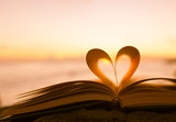 Fototapety Heart from a book page against a beautiful sunset.