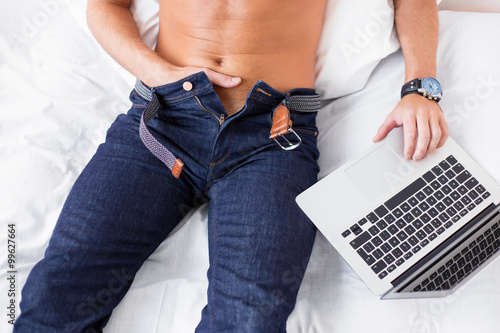 Male masturbating while using computer  - 99627664