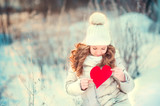cute little girl with a red heart in the hands