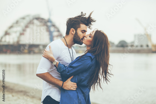Young couple kissing by the river
