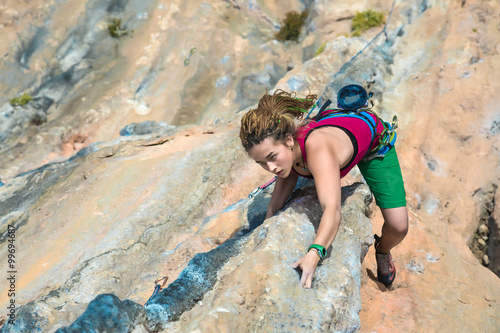 Young Rock Climber ascending steep colorful rocky Wall Lead Climbing
