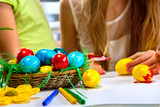 Body part of children paint Easter eggs at home. Focus on eggs. Girl background.