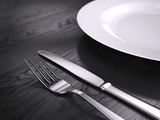 Empty plate, Fork and knife isolated on wooden table