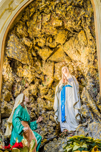 the Blessed Virgin Mary in the grotto at Lourdes Poster