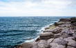 Horizon and rocky coastline with waves splashing under cloudy sk