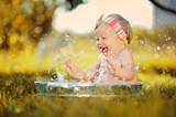 Маленький ребенок играет в тазике с водой