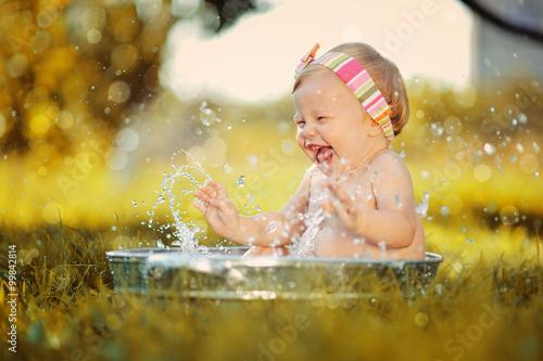 fototapeta na ścianę Маленький ребенок играет в тазике с водой