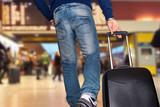 uomo che corre in stazione con valigia trolley per prendere il treno e salirci per viaggio di lavoro
