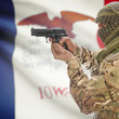 Male with gun in hands and USA state flag on background series - Iowa