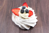 The Meringue cake with whipped cream and fresh blueberries, strawberries on wooden background.