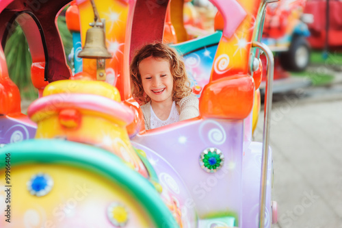 Poster happy child girl riding train on funfair on summer vacation