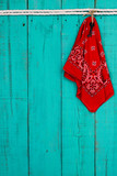 Red bandanna hanging on rustic wood door
